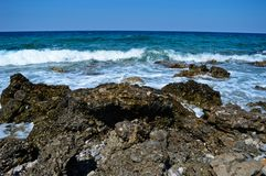 Rocks and waves in Crete, Greece. Rocks and waves in the coast of Crete on a sunny day Stock Photos
