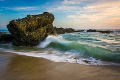 Rocks and waves in the Pacific Ocean at sunset  Royalty Free Stock Image