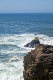 Rocks and waves of surf in the ocean near Farol De Nazare coast Stock Photo