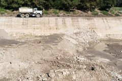 Construction dirt at excavation pit. Rocks and wet soil at excavation site. Blurred truck in background royalty free stock photography