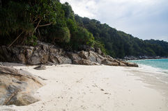 Rocks on white sand Turtle beach at Pulau Perhentian, Malaysia. Relax on a deserted beach in an island of Tropical paradise. White sand Turtle beach with huge Royalty Free Stock Photos