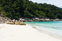 Rocks on white sand Turtle beach at Pulau Perhentian, Malaysia. Relax on a deserted beach in an island of Tropical paradise. White sand Turtle beach with huge Royalty Free Stock Photography