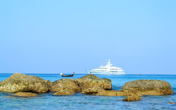 Rocks and yacht with blue sky backgrounds Stock Photo