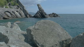 Rocks at Zoagli Beach Italy. A two shot sequence including a medium long and medium wide high dynamic range shallow depth of field tracking slider shots during a stock video footage