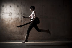 Rockstar in action. Rockstar running with her guitar Royalty Free Stock Images