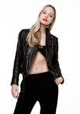 Rockstar biker fashion girl wearing leather jacket. Rockstar biker fashion model girl wearing leather jacket. Long blond hair abd red lips. Studio shot on white Stock Photo