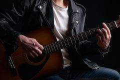 Rockstar in biker leather jacket playing solo on acoustic guitar.  Stock Image