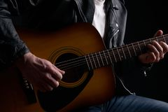 Rockstar in biker leather jacket playing solo on acoustic guitar.  Royalty Free Stock Photo