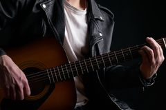 Rockstar in biker leather jacket playing solo on acoustic guitar.  Royalty Free Stock Photography