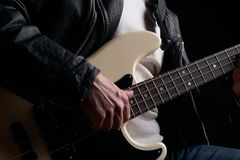 Rockstar in biker leather jacket playing solo on bass guitar.  Royalty Free Stock Image