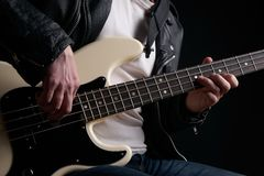 Rockstar in biker leather jacket playing solo on bass guitar.  Royalty Free Stock Photos