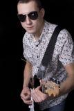 Rockstar con los vidrios que sostienen una guitarra imagen de archivo
