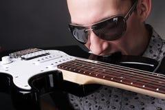 Rockstar, das eine Gitarre anhält Lizenzfreie Stockfotografie