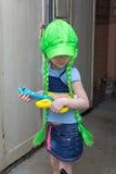 Rockstar des kleinen Mädchens in der Perückenspielgitarre Lizenzfreie Stockbilder