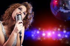 Rockstar. Frau, die in Retro- mic singt Lizenzfreie Stockfotos
