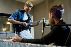 Rockstar gitarrist som komponerar ny sång med producenten fotografering för bildbyråer