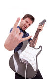 Rockstar holding an electric guitar. Portrait of a successful rockstar holding an electric guitar on white and amking a rock and roll hand gesture Royalty Free Stock Image