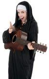 Rockstar Nun. Nun pretending to shoot through her index finger Stock Image