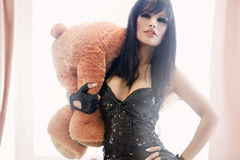 Rockstar's Toys. Young woman dressed like a rockstar holding a teddybear Royalty Free Stock Photo