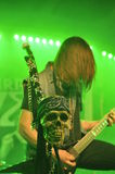 Rockstar skull. Skull in focus, heavy metal rocker in the background with green lights on stage Stock Images