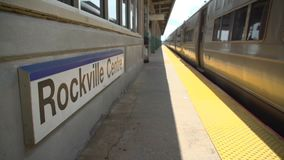 Rockville Centre train passing the station sign. Low view of the Rockville Centre train passing the station sign stock footage