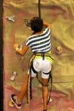 Rockwall climbing. Asian girl climbing a rock wall Stock Photography