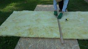 Rockwool do material de isolação da casa do corte do trabalhador no painel de madeira video estoque