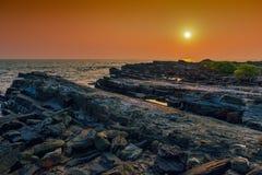 Rocky abandonó y mar tranquilo en la puesta del sol Imagen de archivo