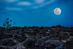 Rocky against blue sky and beautiful full moon at night. Outdoor Royalty Free Stock Photography