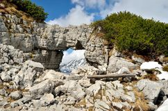 Rocky arch and bench in mountains. Stock Photo