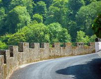 Rocky asphalt road with High stone fence leading to Warfleet lodge, Dartmouth, United Kingdom royalty free stock photo