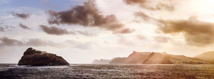 Rocky Atlantic shoreline under dramatic cloudscape. Sunrise on Cape Verde. View from the sea.  Royalty Free Stock Photos