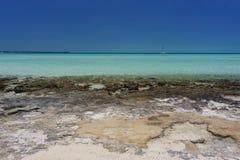 Rocky Bahama Beach with Sailboat Royalty Free Stock Photos