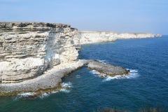 Rocky bank. Cliffs of seashore, high precipice above waves Royalty Free Stock Photo