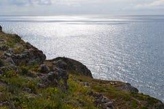 Rocky bank 2. Rocky bank and high precipice, a sun is reflected at sea Stock Photos