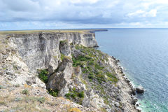 Rocky bank and high precipice. Traveller on verge of rock Stock Photography
