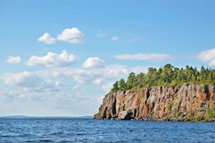 Rocky bank of the Ladoga lake. The high rocky coast of Ladoga lake covered with wood Royalty Free Stock Photos