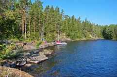 Rocky bank of the Ladoga lake. The rocky coast of Ladoga lake. Sport boats in the distance stock photography