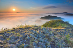 Rocky basalt peak on hill. Forest valley full of gentle fog and Sun above heavy mist. Royalty Free Stock Photography