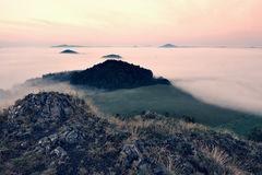 Rocky basalt peak on hill.   Forest valley full of gentle fog and Sun above heavy mist. Royalty Free Stock Image
