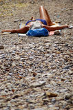 Rocky Beach. A woman resting at the beach Stock Photo