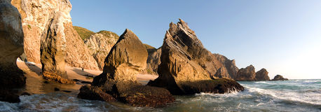 Rocky beach. Panoramic view of a rocky desert beach with low sunset light stock image