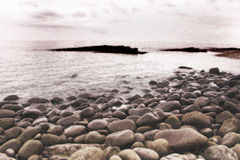Rocky beach. Monochrome grainy picture of a bleak rocky beach royalty free stock photography