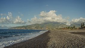 A rocky beach and big green hills under the clouds. Le Port, Reunion Stock Image
