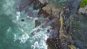 Rocky beach with big waves. Lots of people on the beach. The view from the drone. Green water with waves coming to the shore. Visible foam from the waves stock photography
