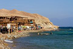 The rocky beach at the Blue Hole, Dahab, Egypt. Scuba divers and tourists on the beach at the Blue Hole, diving spot near Dahab, Sinai Peninsula, Egypt. One of Royalty Free Stock Photo