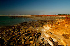 Rocky Beach Broome. Blue water and sky, dark red yellow rocks stock image