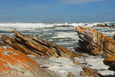 Rocky beach of Cape Agulhas. It is the most southern point of Africa where Atlantic and Indian oceans merge. Orange color over the sharp rocks near the coastline stock photo