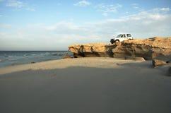 Rocky beach with car. Rocky beach with 4x4 vehicle on a sunny day Stock Photos