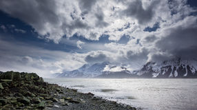 Rocky beach with clouds. Royalty Free Stock Photo